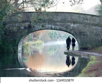 Couple walking under a stone bridge on the Lancaster Canal, Lancashire, England