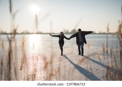 Couple walking while holding hands, landscape view.