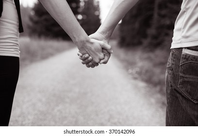 Couple walking while holding hands.