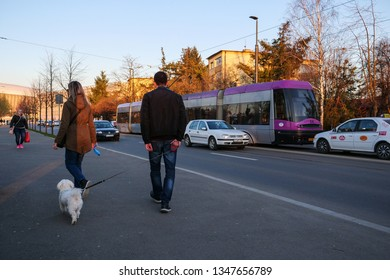Couple walking a white bichon frise on the sidewalk at sunset in Cluj-Napoca, Romania, March 23, 2019