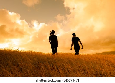 Couple walking in a windy field.