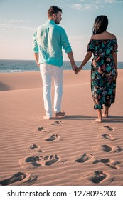 couple walkling sand dunes desert of Maspalomas Gran Canaria, Gran Canary beach Maspalomas sand dunes with men and woman walking desert sand