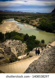 A couple walks down a switchback trail overlooking the Rio Grande as they leave the Santa Elena Canyon. In the distance, hikers stand on the wide clay bank of the river.