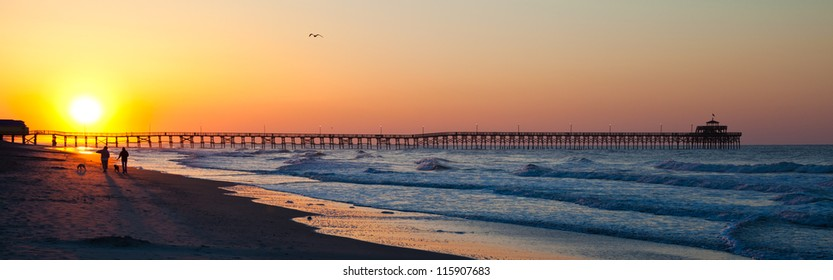 A couple walks their dogs on the beach as the sun rises over the pier at North Myrtle Beach, South Carolina. Creating gorgeous bright colors.