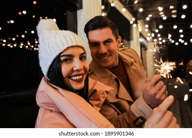 Couple in warm clothes holding burning sparklers near building