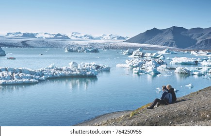 couple in warm jackets sits in Ice Lagoon in Iceland with background of glacier and sky.