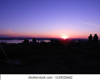 couple watches the sunrise at Cadillac Mountain in Maine, Acadia National park