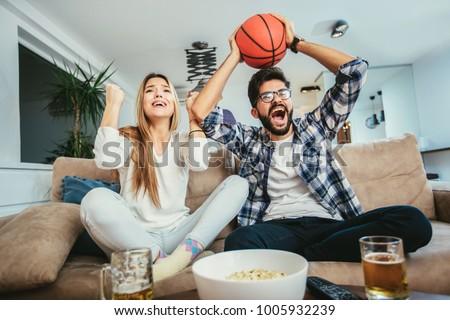 Couple Watching Basketball Game On Sofa Stock Photo Edit Now