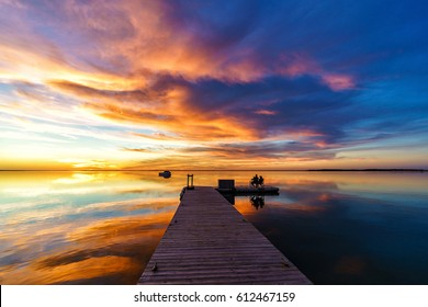 The couple is watching a beautiful sunset on the pier, sunset reflection in the water, sunset clouds.