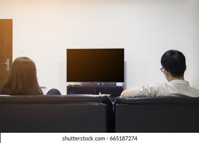couple watching blank TV on sofa