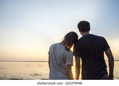 couple watching a colorful sunset on a beach, friendship concept