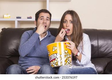 Couple watching film on sofa eating popcorn