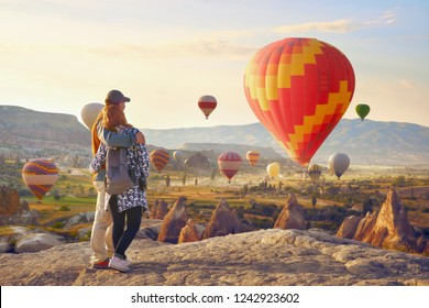 Couple watching the hot air balloons at the hill of Goreme, Cappadocia, Turkey.