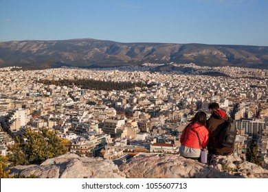Couple watching large city of Athens in Greece