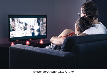 Couple watching movie or series. Online streaming and VOD service in tv screen. Film stream or television show. Cuddling during comfy and romantic candle light date at home. Man and woman relaxing.