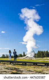 a couple watching on  Old faithful in the morning,summer, in Yellowstone National park,usa.