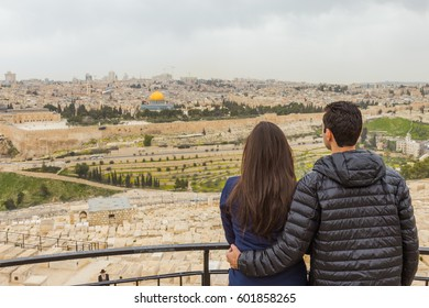 Couple watching the panoramic view of  Jerusalem Old city and the Temple Mount, Dome of the Rock and Al Aqsa Mosque from the Mount of Olives in Jerusalem, Israel.