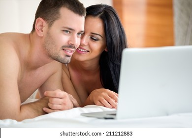 Couple watching porn movie over laptop in bedroom