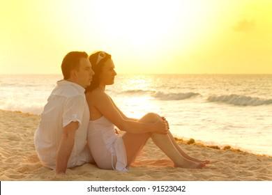Couple watching romantic sunrise on the beach