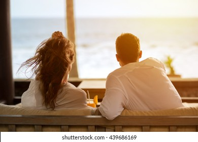 couple watching the sea from the terrace of  their apartment, enjoying in beautiful view