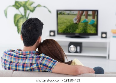 Couple watching soccer game on tv, view from the back