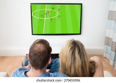 Couple Watching Sports On Television At Home