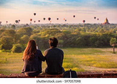 Couple watching sunrise over historic Buddhist temples and stupas in Bagan, Myanmar.