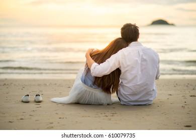 Couple watching sunset in the beach romantic scene