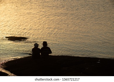 A couple watching the sunset by the shore