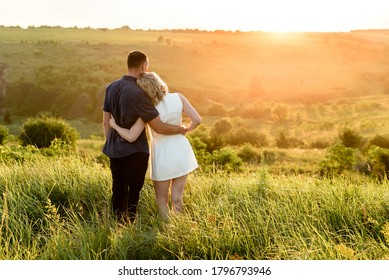 couple watching the sunset in the field