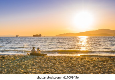 Couple watching sunset on the beach,Vancouver Canada