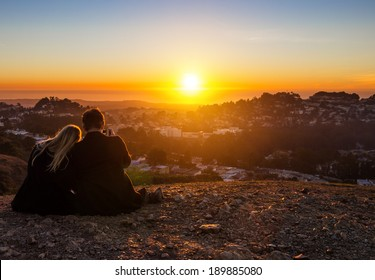 couple watching the sunset on the hill