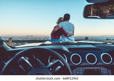 Couple watching sunset from popular view point in Los Angeles, California. Sitting on the sport convertible car hood