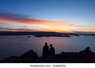 Couple watching sunset from the shore of Lake Titicaca in Peru.