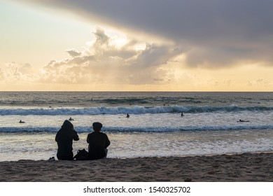 A couple watching surfers on the Coast in autumn near Lisbon