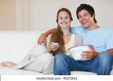 Couple watching television while eating popcorn in their living room