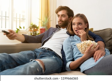 Couple watching TV, eating popcorn on a sofa at home