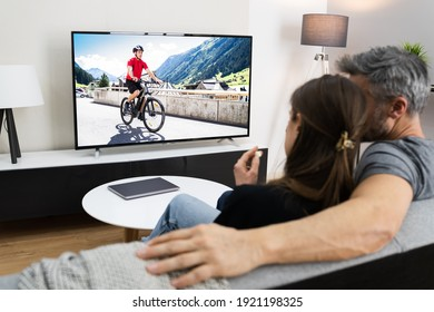 Couple Watching TV Movie On Screen In Room On Couch