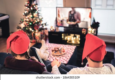 Couple watching tv on Christmas. Happy family holiday at home. Man and woman on couch relaxing with tree, decorations, lights, candles and television. Modern city celebrations. Merry Xmas!
