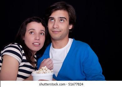 couple watching tv/cinema,  with popcorn, on black background. Studio shot