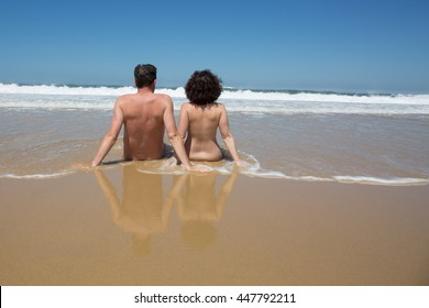 Couple in the water at the beach, backside to camera under blue sky
