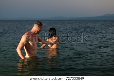 Couple in the water at the beach.Beautiful lady and guy in erotic pose. Nude pictures. Summer time. Sea background. Vacation, travel. Caucasian man. Sexy.
