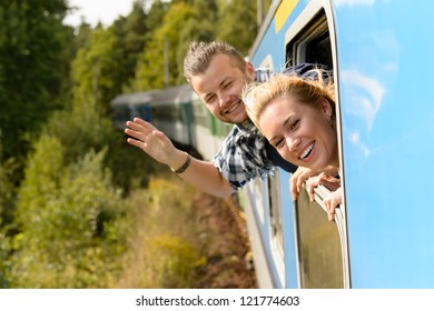 Couple waving with heads out train window enthusiastic carefree happy