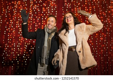 Couple waving for photo in front of light wall at Christmas market.