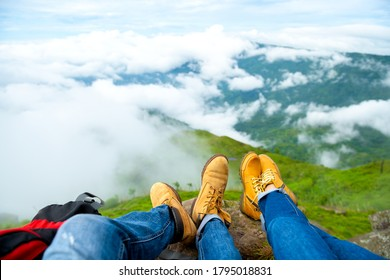 A couple wear brown leather shoes sitting on an overhanging rock enjoying the morning fog over hills and the forest view. - Shutterstock ID 1795018831