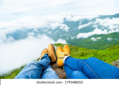 A couple wear brown leather shoes sitting on an overhanging rock enjoying the morning fog over hills and the forest view. - Shutterstock ID 1795488355