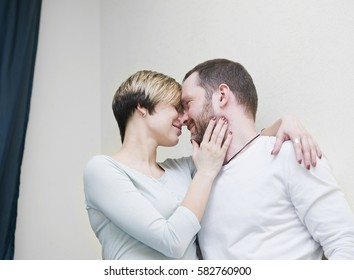 A couple, wearing casual wear, hugging, cropped indoor portrait