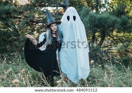 Couple wearing in costume witch and ghost standing in autumn forest outdoor. Theme of Halloween