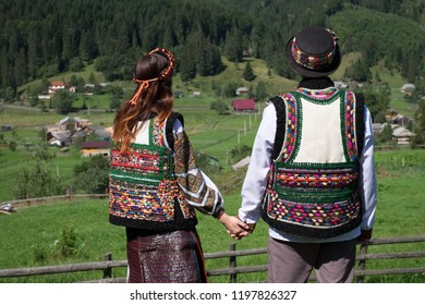 Couple wearing ethnic and traditional of the Carpathian Ukrainian clothes. Mountain village background