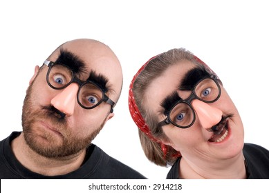 Couple wearing fake nose and glasses with mustashe and eyebrows over a white background